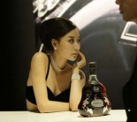 A bottle of Hennessy X.O. is displayed next to a model at  theTop Essence luxury goods show in Beijing